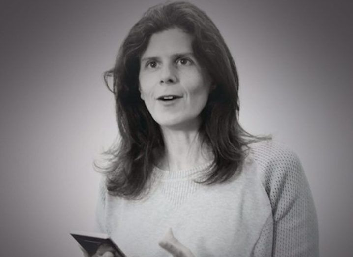 A black and white image of a woman with dark hair holding a smartphone and looking beyond the camera.