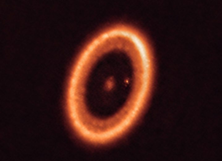The PDS system is pictured. The star is at the centre and PDS 70c can be seen to the right of the star. All of the bodies are orange, and the picture is primarily a large, circumstellar disc that surrounds the planets and the star.