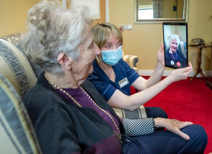 A woman in a nursing home sits in a chair while a nurse wearing a face covering holds up a tablet showing the face of another woman.