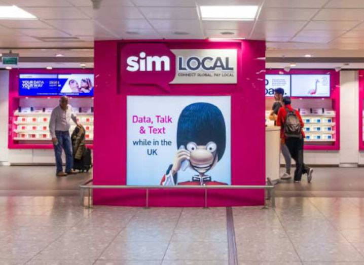 Travellers in an airport browse a Sim Local store, looking for local SIMs to avoid roaming charges.