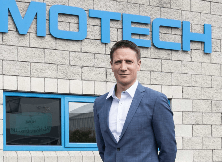 A man in a suit stands outside a building during the day. On the building is part of the SimoTech logo in blue.