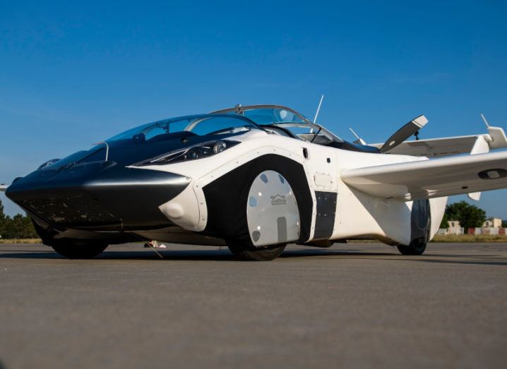 The AirCar is shown on the ground. Its wings are deployed and its tail can be seen on the back. Aside from these, it resembles a regular sports car convertible, with glass over the cockpit.