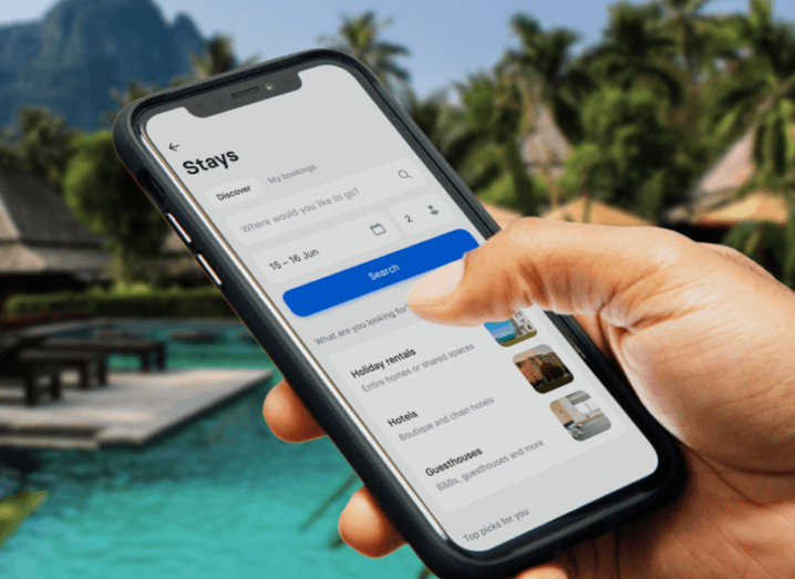 Someone is holding a phone while on holiday. The Revolut Stays app is open on the screen while a swimming pool and palm trees can be seen in the background.