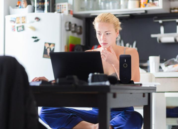 Woman sitting cross-legged at kitchen table working on a computer. There is a router beside the computer bearing the Vodafone logo.