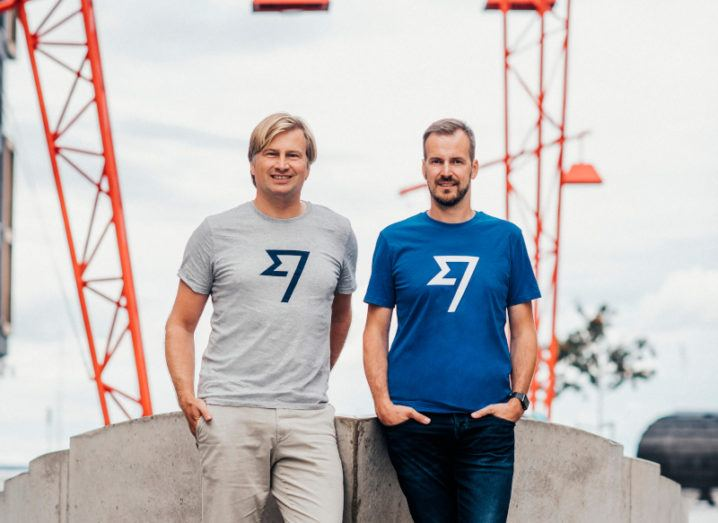 Two men stand outside by a low cement wall. They are both wearing T-shirts bearing the Wise logo.