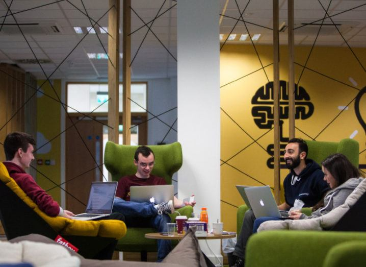 Three men and a woman sit in a round of lime-green high-backed chairs, working on laptops in a vibrant office space.