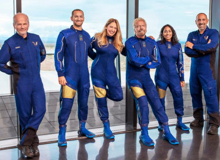 The crew of the VSS Unity are pictured standing and smiling. They are all wearing identical blue jumpsuits and are leaning against a glass wall. A runway can be seen through the glass.