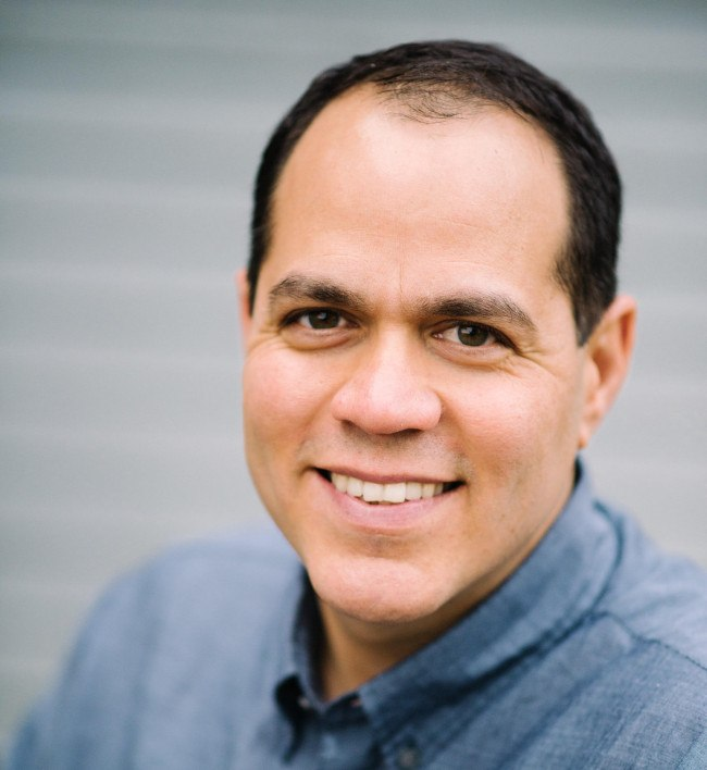 A headshot of Yashar Behzadi, the CEO of Synthesis AI. He is smiling at the camera.