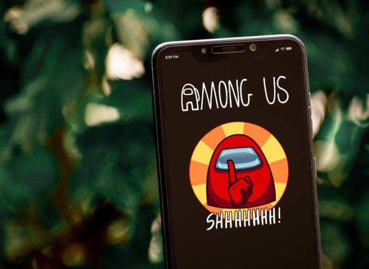 The video game Among Us is shown on a smartphone. The text 'Among Us' is above a red figure, who has his finger to his lips. 'Shhh' is written underneath the figure.