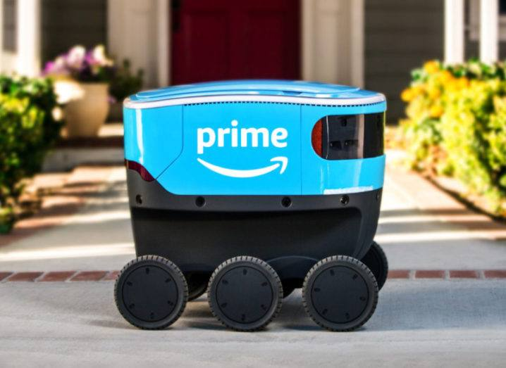 A Scout delivery robot, which looks like a cooler on wheels, bearing the Amazon prime logomark.