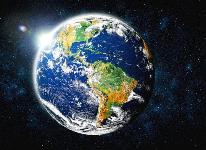 The Earth is pictured in space with the sun behind it. The colours of the planet are vivid, with the continents and oceans clearly visible and clouds floating across the globe.