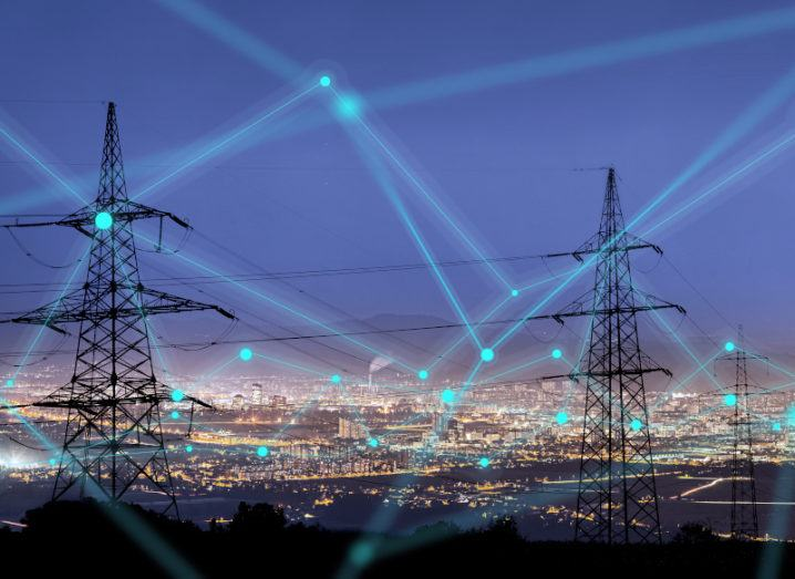 High power electricity poles in urban area are shown connected via wires. City lights are in the background, and green lines are superimposed over the image to represent the energy connectivity.