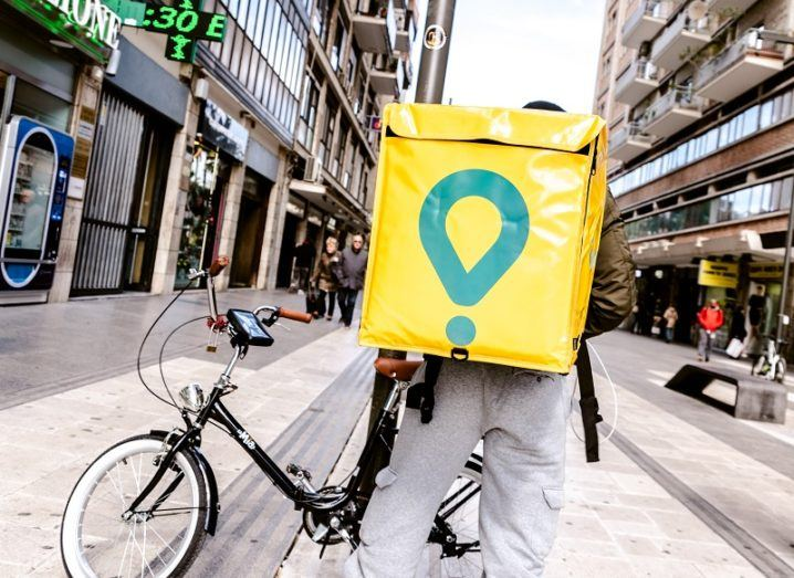 A man with a bike wearing a Glovo backpack is standing on an Italian city street.