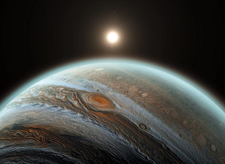 The curvature of Jupiter can be seen from space. There is a blue aura around the planet, and the sun can be seen in the background. The clouds of Jupiter can be seen and are brown and white.