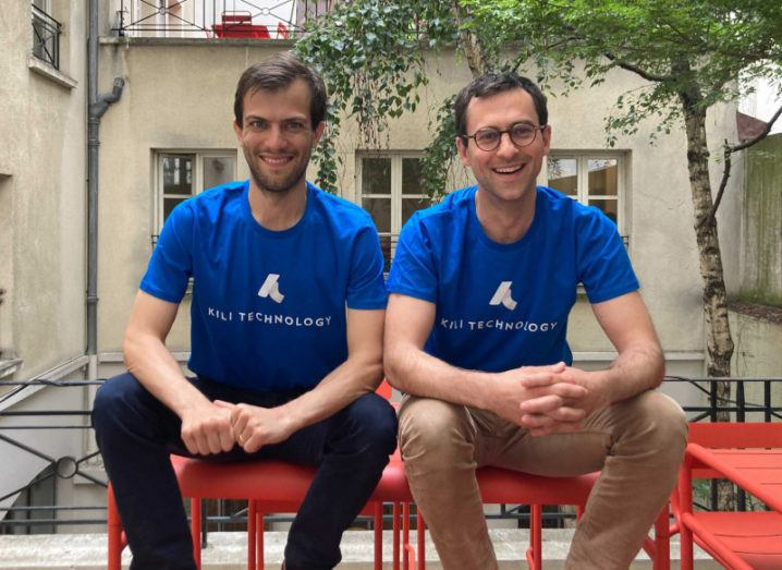 Two men in blue Kili Technology T-shirts sit on a red bench outside a building.