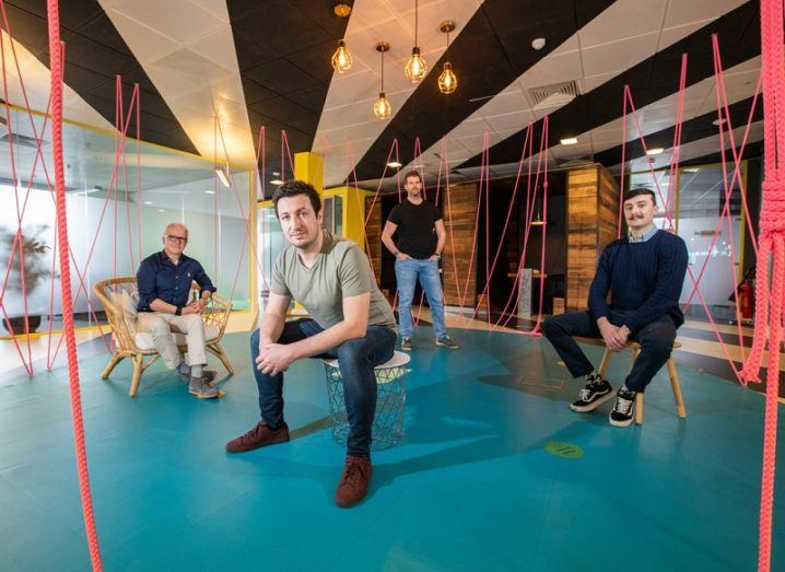 Four men sit in a colourful office space.