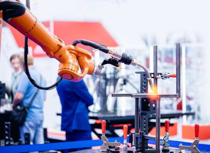 An orange robot hand performs welding work on metal structures in a manufacturing warehouse.