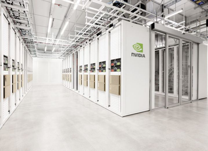 The NVIDIA Cambridge-1 supercomputer is pictured. There are white and cream covered computer clusters in a line, showing the large facility with over 80 systems integrated together.