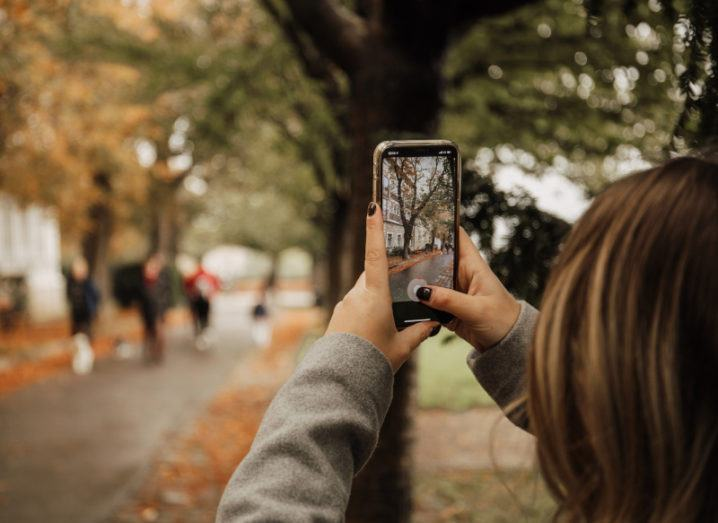 A woman is pictured taking a photograph on her phone. The image on the phone screen is in-focus and a tree and building are in her shot. The leaves of the trees are orange, with many on the ground, suggesting it is autumn.