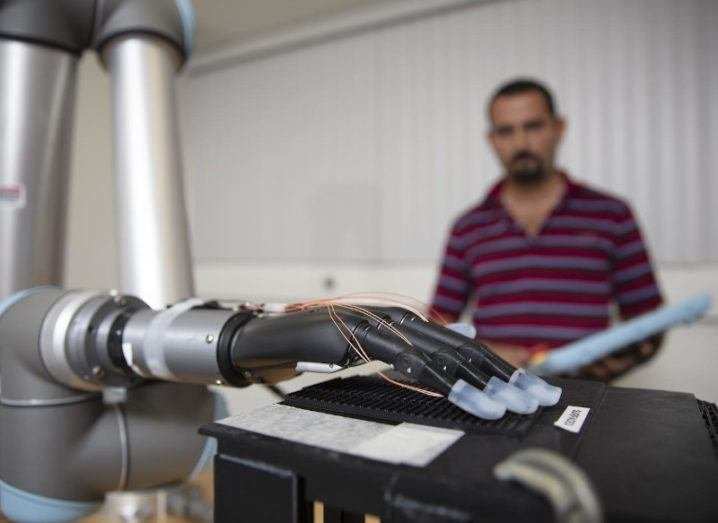 A prosthetic limb is touching a surface to investigate its texture. There are clear coverings over each of the fingertips and wires are running from these. A researcher is sitting behind the arm, but is out-of-focus in the shot.