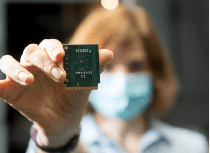 Close-up of a computer chip being held up by a woman, who is out of focus in the backgroun, wearing a face mask.