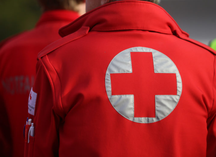 The backs of two medics in the Red Cross are shown. They are facing away from the camera, but the Red Cross logo is clear on the back of their jacket.