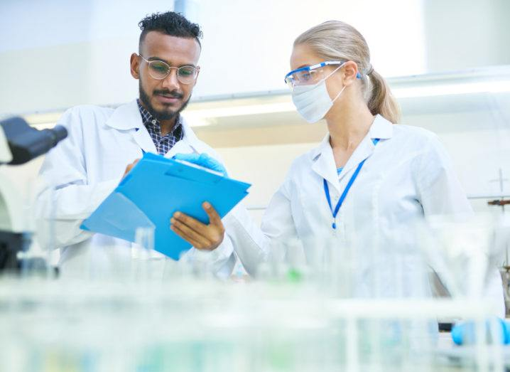 Two scientists are in the lab working together. A man is on the left and is holding a clipboard. A woman is on the right and is wearing safety glasses and a mask while pointing to the clipboard.