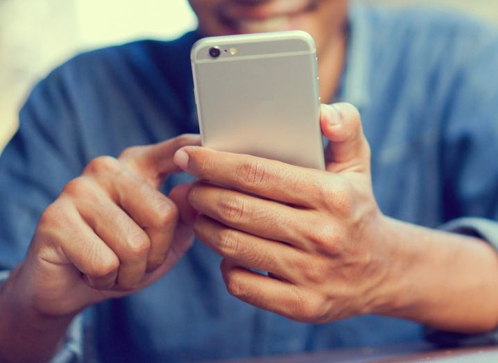 A person wearing a blue shirt holds a smartphone.