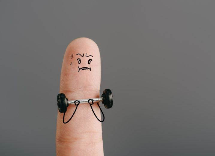A sweating cartoon figure is drawn in black pen over a finger. They are lifting a barbell and struggling with the weight. They have a furrowed brow, a headband on the catch sweat and have two sweat droplets from their forehead.