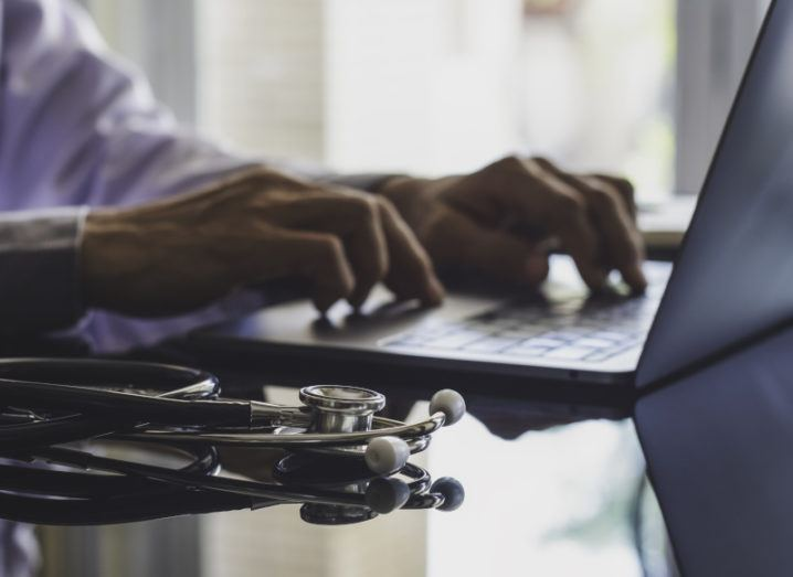 A man with a doctor's coat sits at a table working on a laptop while a stethoscope sits beside him.