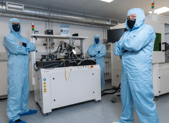 Three people stand in blue full-body lab overalls. They are distanced and are wearing masks. They are all standing with their arms crossed and a photonics machine is in the middle of the group.