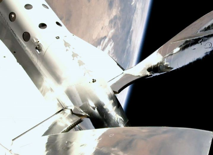 The VSS Unity is pictured in space. The Earth can be seen in the background. The body of the spacecraft can be seen with windows dotted along the central body.