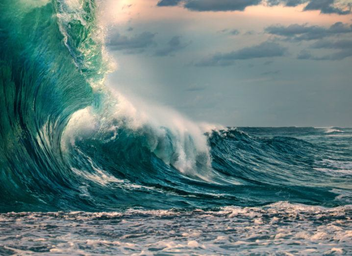 A large wave in the ocean is depicted. There is some white froth, but most of the water is a dark blue with a green hue. The sky is a light grey with hints of orange and the occasional cloud.