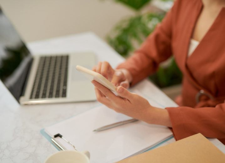 A woman is sitting at a desk holding her phone. Her laptop is on the desk in front of her, and there is a legal pad beside it. She is wearing an orange jacket and a white top.
