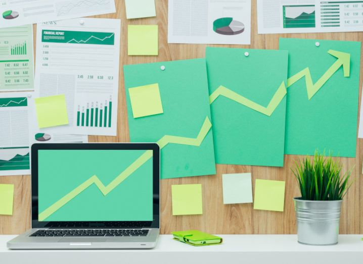 Successful financial chart with arrow pointing up composed of green paper cuts hanging on a wall and laptop, eco business and financial success concept.