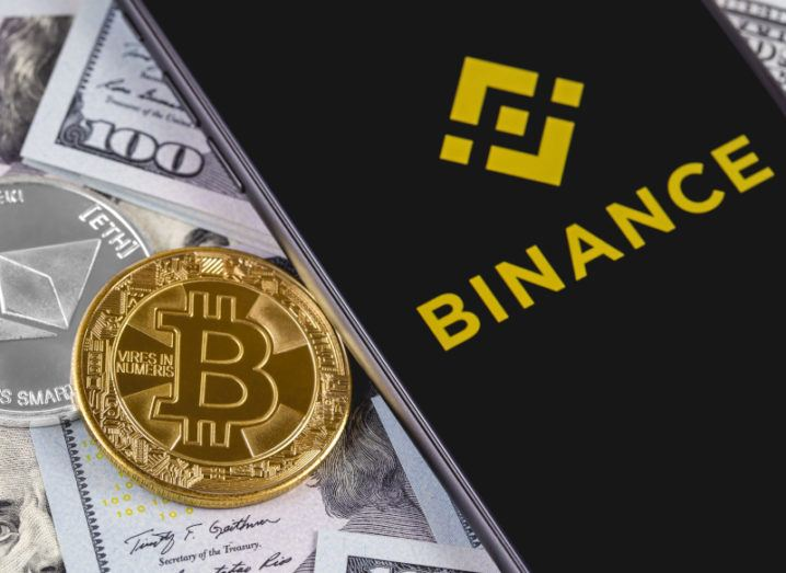 The Binance logo on a phone, positioned on top of a pile of US dollars, and Bitcoin and Ethereum coins.