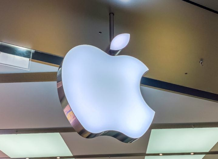 Apple logo suspended from ceiling in a shopfront made from glass.