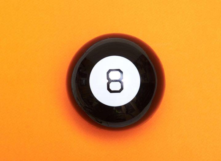 A magic eight ball against a bright orange background.