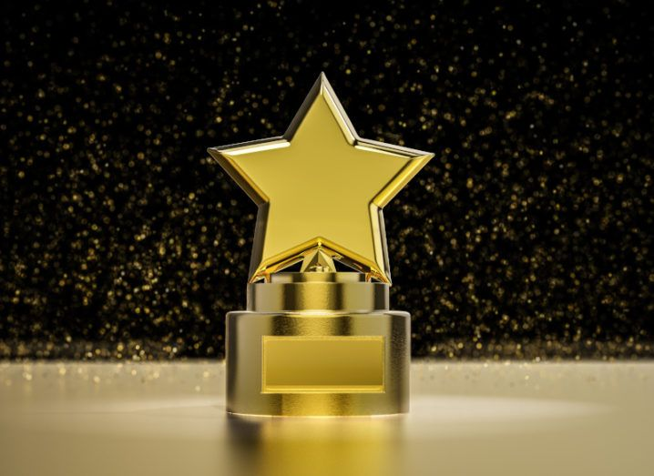 A gold trophy with a star on top of it sits against a black background.