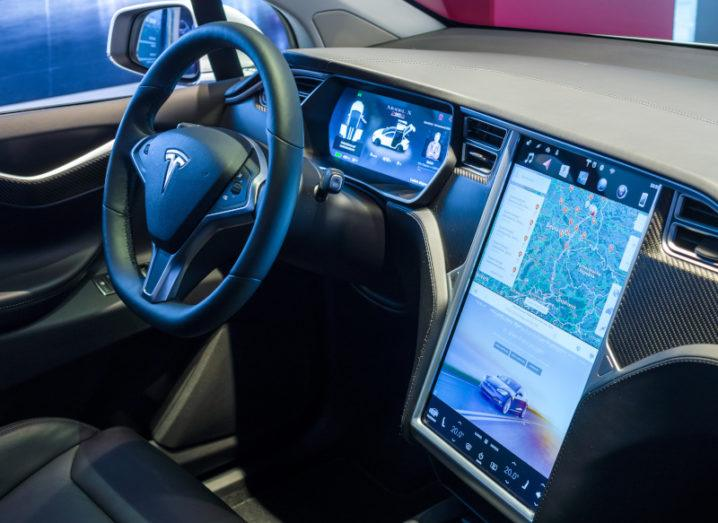 The interior of a Tesla Model X, showing a steering wheel and a computer panel.