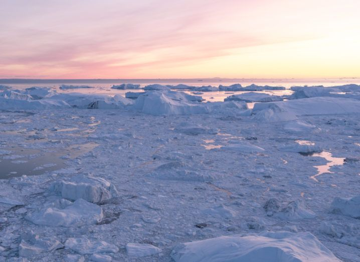 Glaciers melting against a pink and yellow sunset.