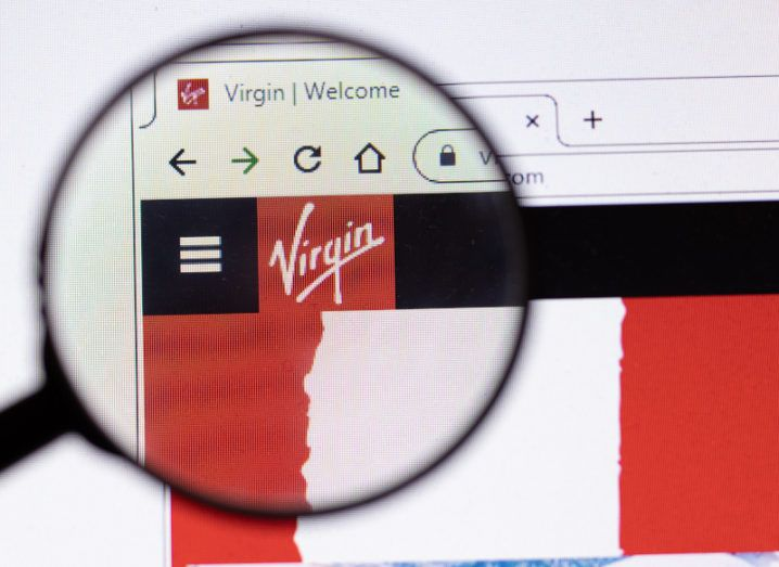 Magnifying glass focused on a webpage displaying Virgin Media's typeface logo on a Google Chrome browser.