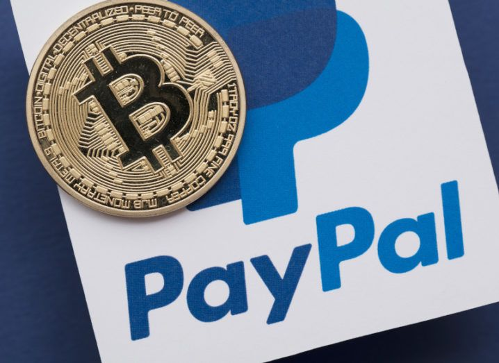 A Bitcoin coin sitting on top of the PayPal logo.