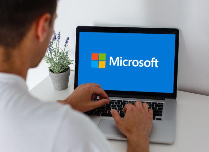 Man working at a laptop displaying Microsoft logo.