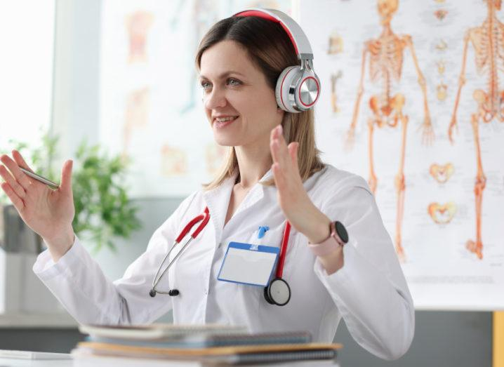 Scientist/doctor doing a remote consultation or lesson in a classroom surrounded by anatomy posters and wearing a stethoscope indicating she is a doctor or medical professional.