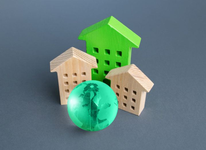 Three wooden models of houses, one painted bright green, stand grouped around a glowing green globe against a muted grey background.
