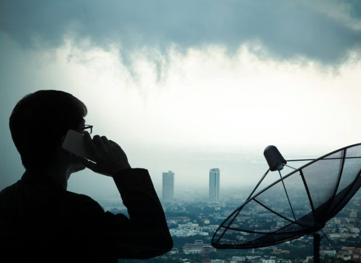 A man using a smartphone with a satellite dish and stormy cityscape in the background.