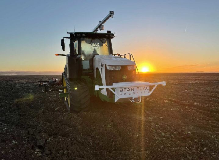 A John Deere and Bear Flag tractor with a sunset in the background.