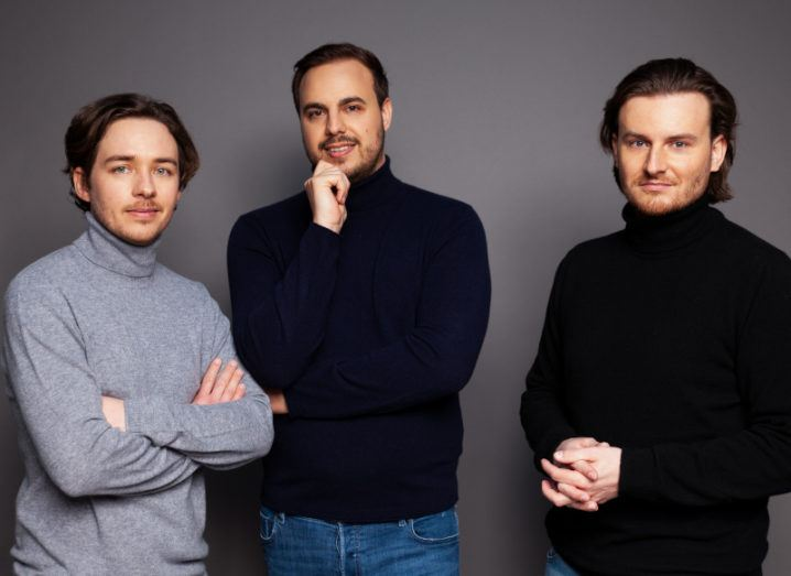 Three men in high neck jumpers stand against a dark background.