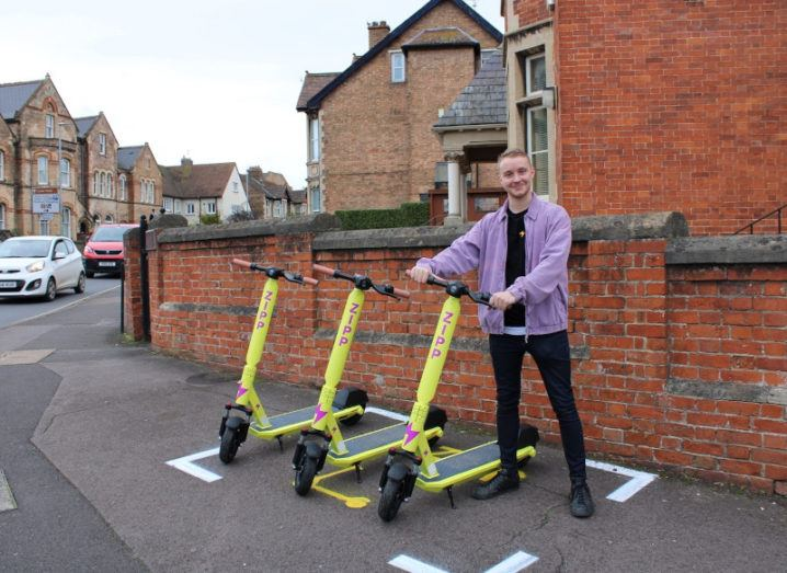 Zipp Mobility founder Charlie Gleeson posing with a number of the company's scooters.